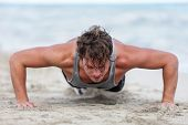 Fit fitness man exercising arms muscles doing exercise push ups exercises. Caucasian male fitness at poster