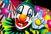 picture of circus clown  - Very bright coloured face of a clown seen lite up by neon lights seen at amusement parks fairs and showtime - JPG