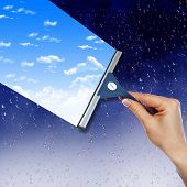 stock photo of cleaning service  - Hand with squeegee cleaning the  misted window - JPG