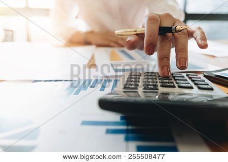 poster of Close Up Business Woman Using Calculator And Laptop For Do Math Finance On Wooden Desk In Office And