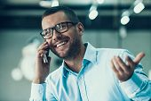 Young Smiling Businessman Talking On Phone. Happy Man Wearing Glases And Blue Shirt Talking On Smart poster