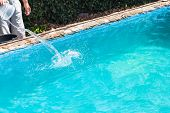 Man Pours Of Disinfectant In Outdoor Swimming Pool On Backyard Of Country House poster