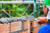 Construction Worker Using Trowel To Add Cement Mortar On Top Of The Stacked Terra Cotta Bricks To Pr poster