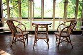 An Old Wicker Bistro Table And Chair Set Sits Empty In A Sun Room Patio Of A Large Historic House. poster
