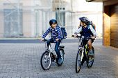Two School Kid Boys In Safety Helmet Riding With Bike In The City With Backpacks. Happy Children In  poster