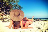 Summer beach photo. Woman on vacation. Beautiful girl on beach. Young woman in bikini under sunlight poster