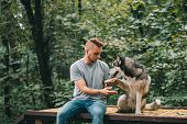 Handsome Man Holding Paw Of Obedient Siberian Husky Dog poster