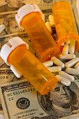 foto of top-less  - Open bottle of pills spilling out on top of US currency along with empty bottles - JPG