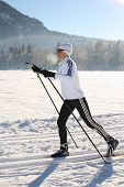 pic of nordic skiing  - Nordic skating woman in front of mountains.