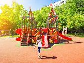 The Boy Is Having Fun On The Street Playground. Swings And Slides In The Park For Children. Children poster
