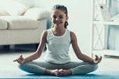 Smiling Little Girl Doing Yoga Pose At Home. Adorable Happy Child In Sportswear Sitting On Yaga Mat  poster