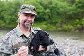 Постер, плакат: Среднего в возрасте человек с собакой Русский охотничий спаниель На берегу реки Дождь