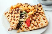 A calzone-style covered pita pie, containing chicken souvlaki meat, salad and cheese, served with fr