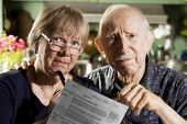 pic of elderly couple  - Worried Elder Couple at Home with Bills - JPG