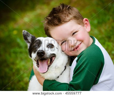 Child lovingly embraces his pet dog, a blue heeler poster