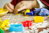 pic of molding clay  - Closeup of colorful plasticine molds and child hands playing on the background - JPG