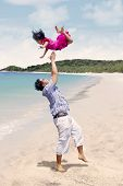 Father throwing daughter in air at beach