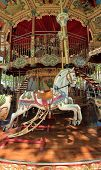 stock photo of carousel horse  - View of the inside of a colorful carousel with beautiful white horses - JPG