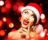 Christmas Woman. Beauty Model Girl in Santa Hat over Glowing Holiday red Background. Funny Laughing