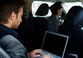 foto of limousine  - Young man in limousine working on laptop computer - JPG