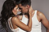 picture of hand kiss  - Beautiful young smiling couple in love embracing indoor - JPG