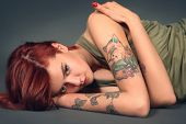 Picture of young tattooed girl on dark background.