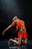 image of dancing rain  - Woman dancing under rain in orange dress - JPG