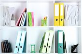White office shelves with folders and different stationery, close up
