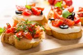 Italian Appetizer Bruschetta with roasted tomatoes, mozzarella cheese, garlic and herbs