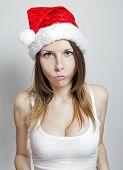 stock photo of sad christmas  - Sad young girl in a christmas hat on white - JPG