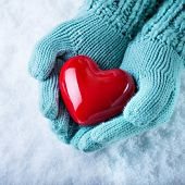 Woman hands in light teal knitted mittens are holding a beautiful glossy red heart in a snow backgro