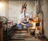 stock photo of levitation  - Stressful Businessman levitating in yoga lotus pose with alarm clock in his hand in old Russian house with traditional stove - JPG