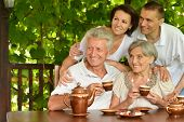 image of stepmother  - Happy family drinking tea at table outdoors in summer time - JPG