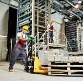 foto of paving stone  - Young worker moving paving stones with pallet truck on a factory - JPG