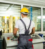 picture of heavy equipment operator  - Operator wearing safety hat in a factory control room - JPG