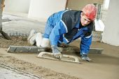 stock photo of floating  - Plasterer at indoor concrete cement floor topping with float - JPG