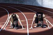 stock photo of sprinter  - Sprinter couple in start position illuminated by a spotlight - JPG