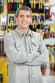 picture of hardware  - Portrait of happy mature man standing arms crossed in hardware store - JPG