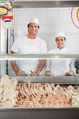 pic of slaughterhouse  - Portrait of confident male and female butchers smiling at display cabinet in shop - JPG