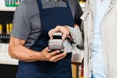 picture of hardware  - Male customer paying with mobilephone using NFC technology in hardware store - JPG