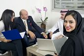 stock photo of hijabs  - Arabian Businesswoman in office with Businesspeople meeting in the background - JPG