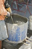 Постер, плакат: an unidentifiable contractor mixes stucco in a blue plastic drum in preparation of applying it to a