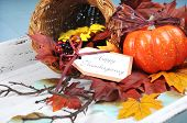 picture of cornucopia  - Happy Thanksgiving cornucopia with Autumn Fall leaves pumpkin sunflower and berries on white shabby chic tray against a pale blue background - JPG