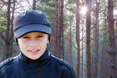 stock photo of boy scout  - child boy backlight portrait pine forest outdoor - JPG