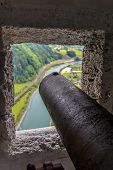 stock photo of cannon  - An old cannon and a view through the castle