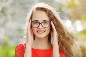 stock photo of charming  - Charming young smiling girl in glasses outdoors - JPG