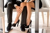 image of flirt  - Young couple flirting with legs at the restaurant under the table - JPG