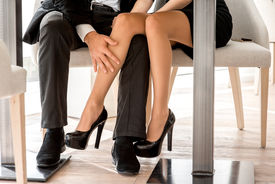 picture of flirt  - Young couple flirting with legs at the restaurant under the table - JPG