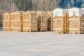 foto of cleaving  - Solid biofuel as fire wood made of birch stacked on pallets in outdoor stock - JPG
