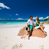 image of couple sitting beach  - Couple in green sitting on a rock at tropical Seychelles beach - JPG